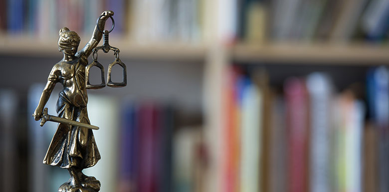 Justice figurine in front of books belonging to a New York criminal defense lawyer