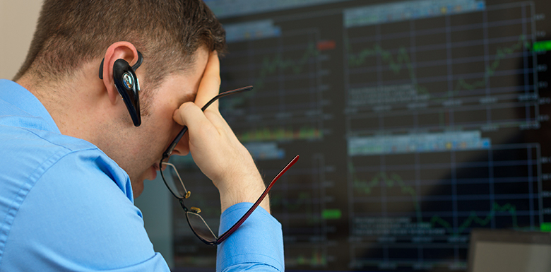 Stock broker looking at computer screen with his head in one of his hands